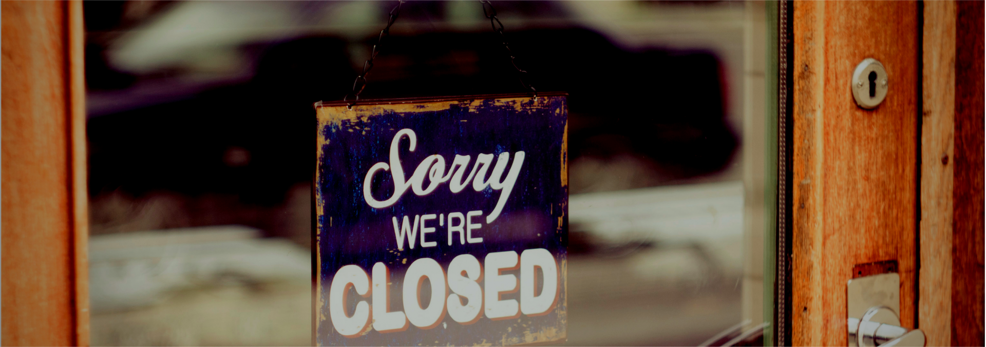 A closed sign hangs in a business window.